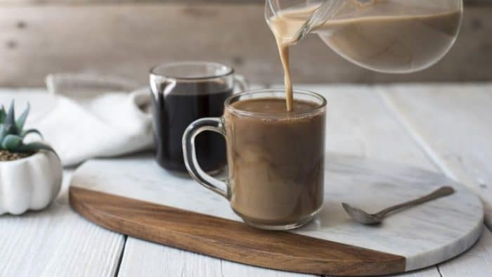 a vegan coffee creamer pouring over a mug of black coffee