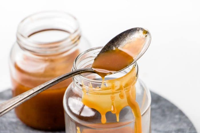 a spoon with dripping caramel sauce which will be used in making vegan coffee creamer