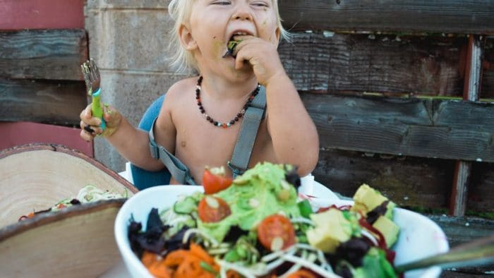 kid enjoys eating vegetables