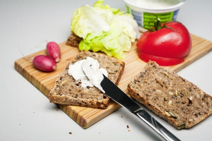 butter spread into a slice of bread plus other fresh vegetables used for making sandwich