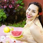 woman holding plate of sliced watermelon