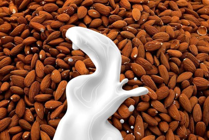 plant-based milk: milk splashes down onto almonds