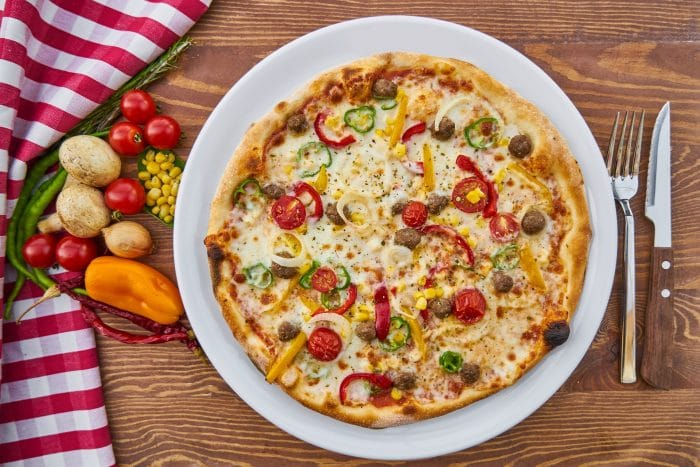 pizza hut vegan cheese: a vegan pizza next to vegetables and cutlery on a wooden table