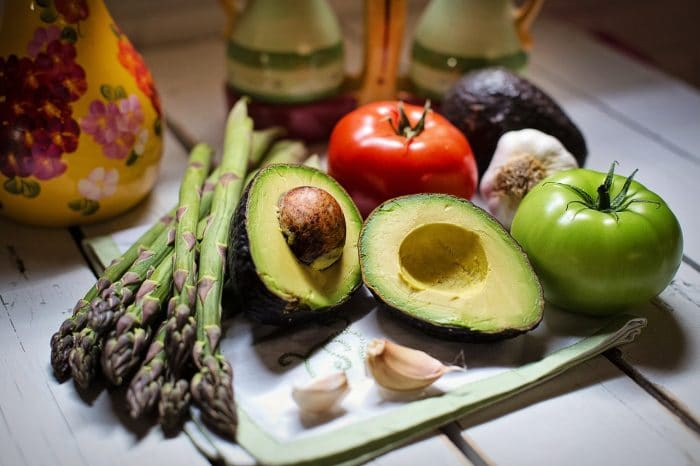 What You Can Eat as a Vegan at a Restaurant That's Not Salad: asparagus, tomatoes, avocados, and other foods appear on a cutting board