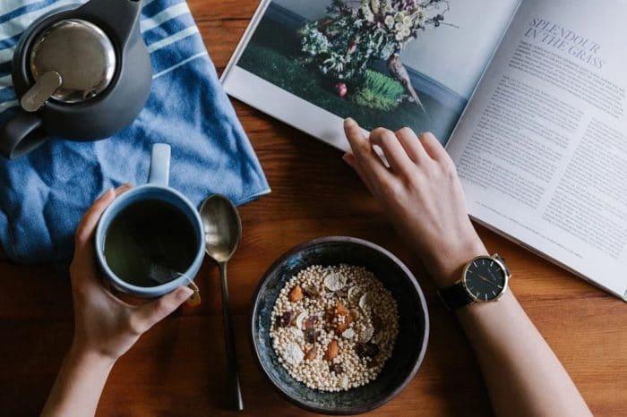 woman eating vegan food reading book, wondering about arguments against veganism